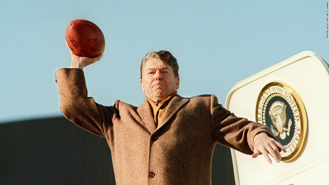 President Ronald Reagan throws a football toward the press before boarding Air Force One in 1988.
