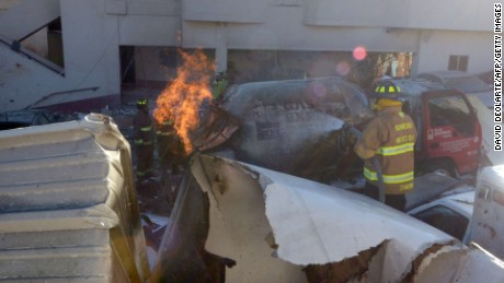 Firefighters battle flames in the debris from the explosion.