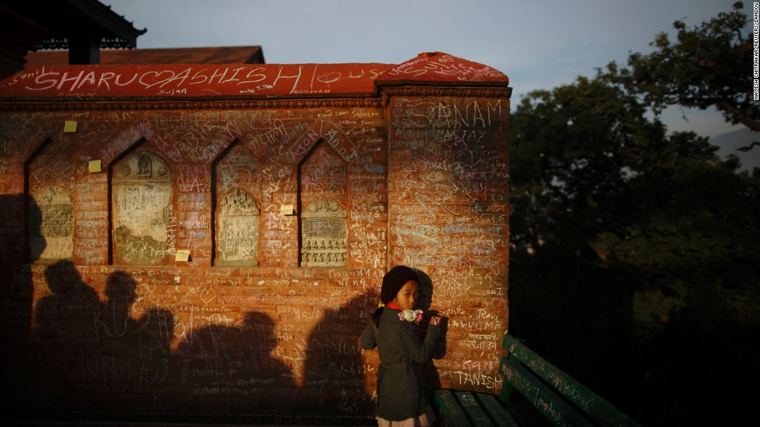 A girl looks at her mother as she writes on the wall of the Saraswati temple Sunday, January 25, during the Shree Panchami festival in Kathmandu, Nepal. Children are given their first reading and writing lessons at the temple in the belief that Saraswati, the Hindu goddess of education, will help them excel.
