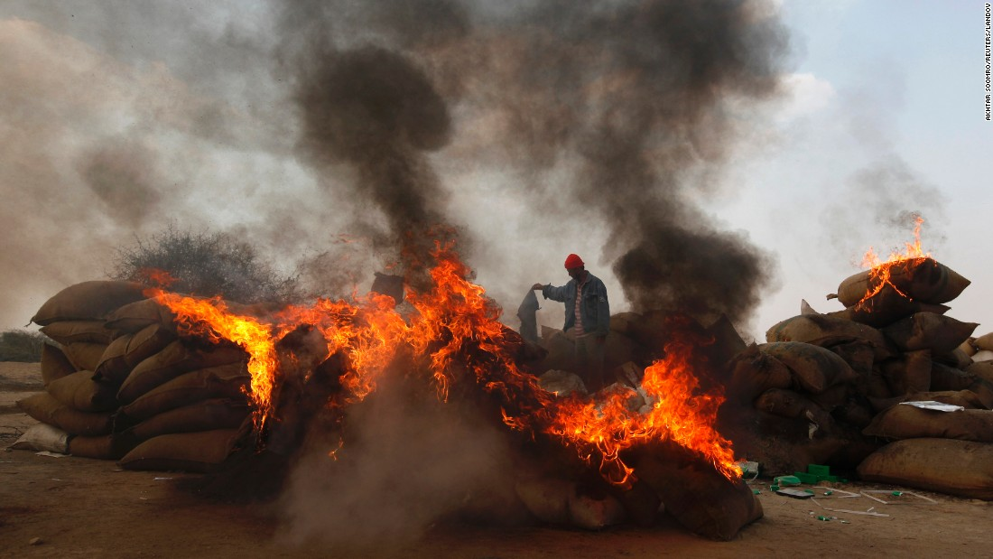 A man from the Pakistan Customs department stands amid burning piles of narcotics and contraband on the outskirts of Karachi, Pakistan, on Monday, January 26. The department destroyed the contraband in an exercise to mark International Customs Day, official Qamar Thalho said.