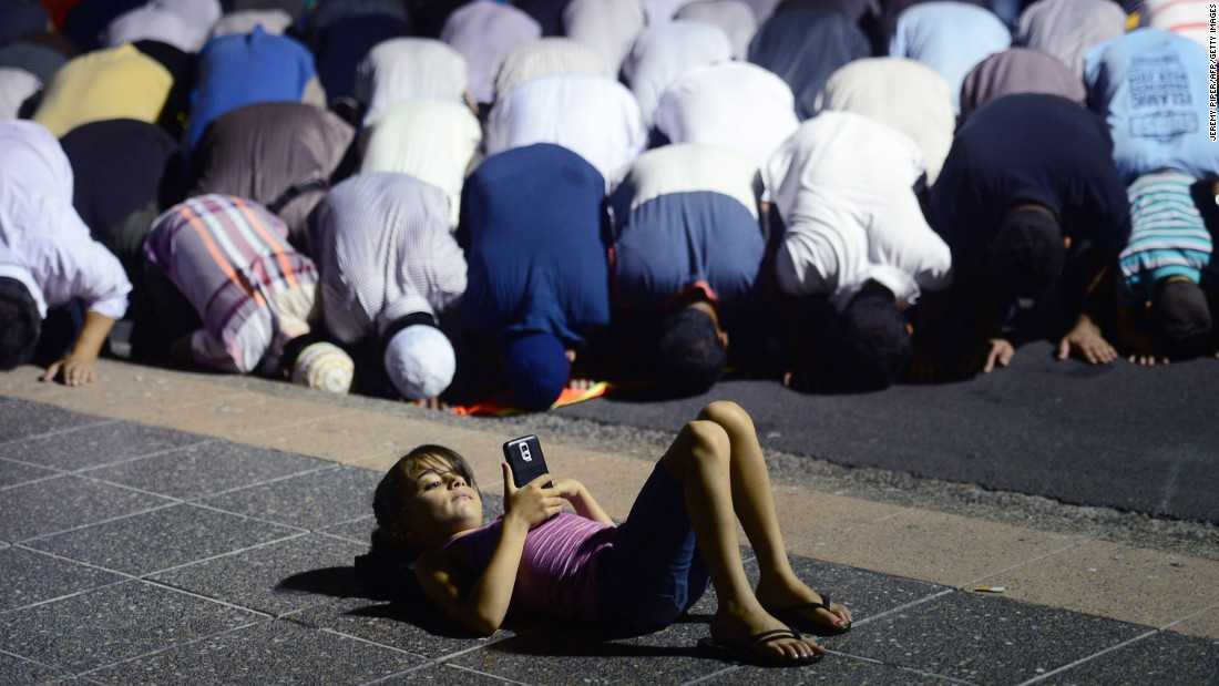 "A young girl in Sydney plays on her phone Friday, January 23, as Muslims pray during a rally <a href=""http://www.cnn.com/2015/01/20/world/gallery/charlie-hebdo-cover-protests/index.html"" target=""_blank"">protesting negative coverage of Islam</a> and Charlie Hebdo's caricatures of the Prophet Mohammed. In early January, 12 people were <a href=""http://www.cnn.com/2015/01/07/world/gallery/paris-charlie-hebdo-shooting/index.html"">killed in a terror attack</a> at the Paris office of Charlie Hebdo, a French satirical magazine. Following the attack, the magazine released a new edition featuring the Prophet Mohammed on the cover. He was holding a sign saying ""Je suis Charlie"" (""I am Charlie"")."