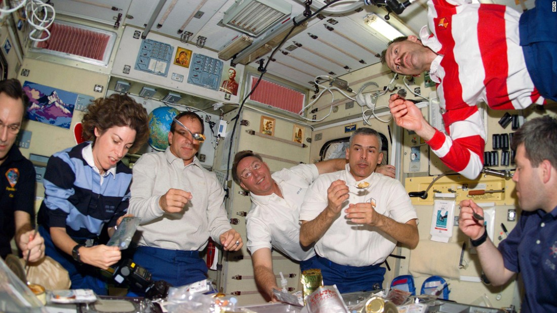 Astronauts floating around at meal time. On the International Space Station astronauts eat at a fold-down table, with food items secured with Velcro or bungee cords. But what do they actually eat?