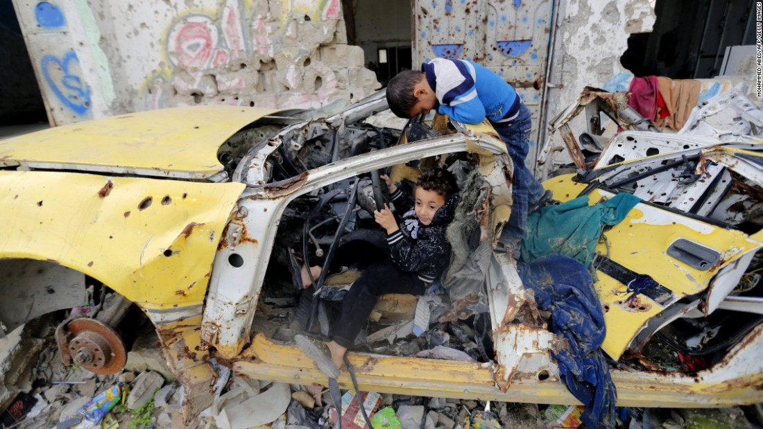 "Palestinian children in Gaza City play together Tuesday, January 27, next to buildings that were destroyed last year during <a href=""http://www.cnn.com/2014/07/18/world/gallery/israel-gaza/index.html"" target=""_blank"">fighting between Israel and Hamas.</a>"