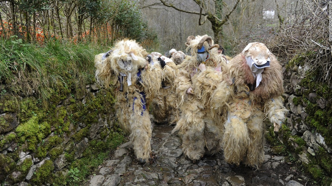 People wear sheepskin disguises as they take part in the ancient carnival of Ituren, Spain, on Monday, January 26.