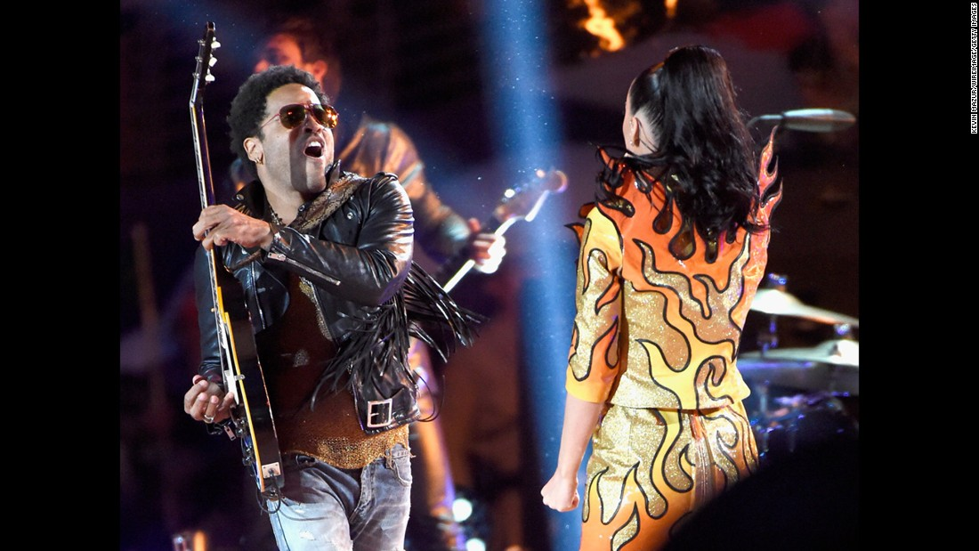 "Lenny Kravitz plays the guitar on stage with Perry as she sings ""I Kissed a Girl."""