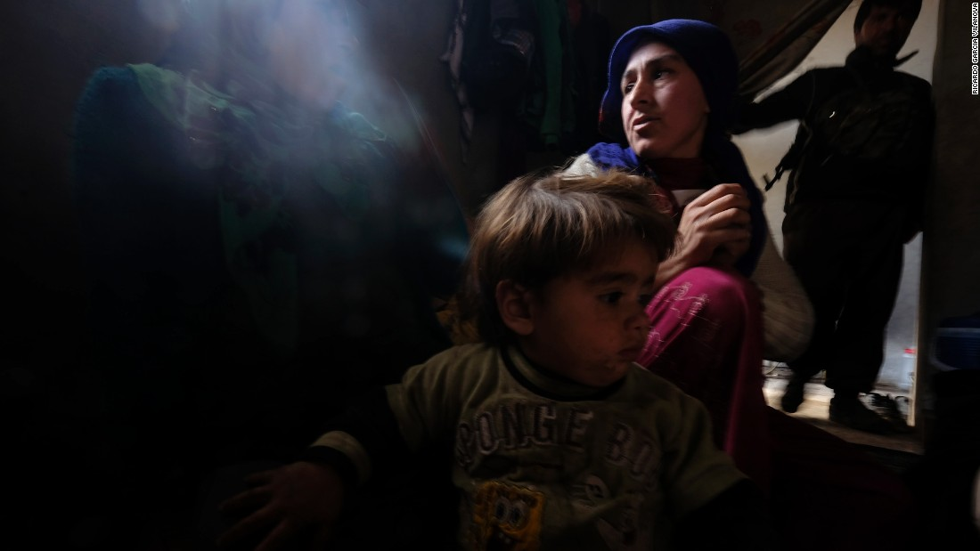 "Zehra, a 25-year-old Kurdish woman who lost her 8-month-old daughter due to a lung infection at a refugee camp, sits with her other daughter inside their home in Kobani, Syria, on Thursday, January 29. Her husband, a fighter from the People's Protection Units, or YPG, stands in the background. After four months of intense fighting, Kurdish Peshmerga forces <a href=""http://www.cnn.com/2015/02/04/middleeast/kobani-syria-destruction/index.html"" target=""_blank"">have liberated Kobani</a> from the grip of the ISIS militant group. Click through to see more photos of Kobani taken recently by Ricardo Garcia Vilanova."