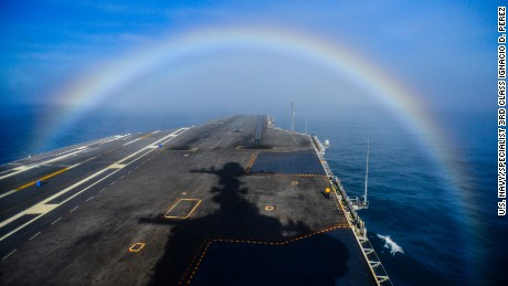 A rainbow forms over the bow of the Nimitz-class aircraft carrier USS John C. Stennis.
