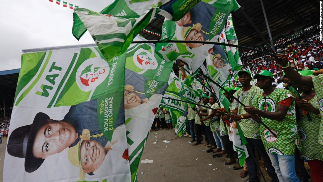Supporters at a PDP rally in the Niger Delta wave flags bearing President Jonathan's portrait on January 28.<br />