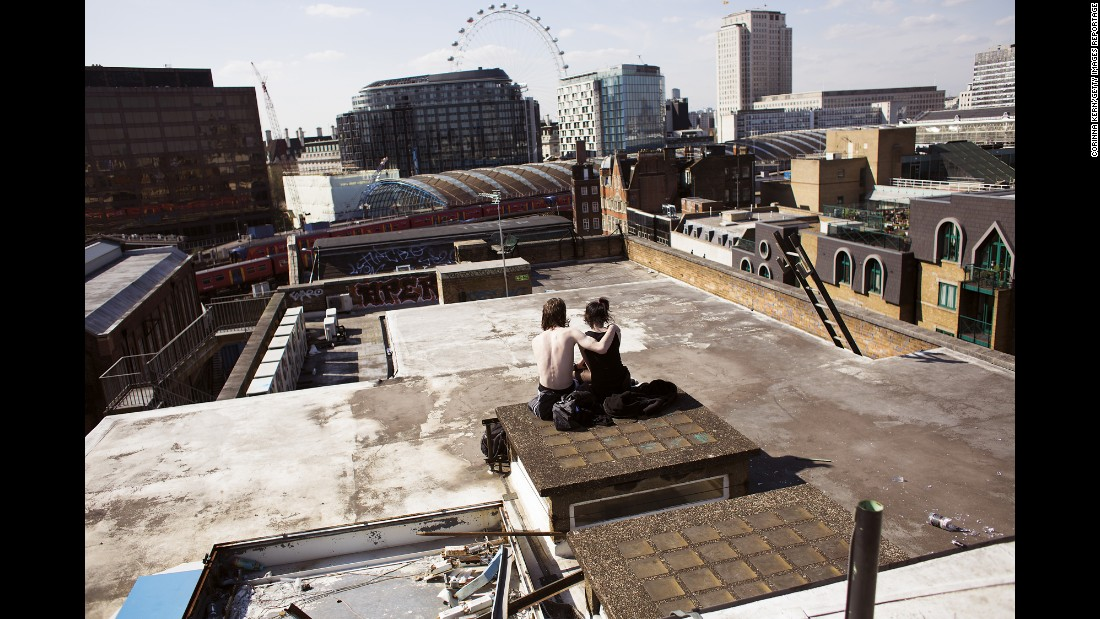 "A couple sits on the rooftop of a squat in London called ""The Castle."" Once used as a five-story office, the building has become home to more than 100 squatters -- people who don't pay rent."