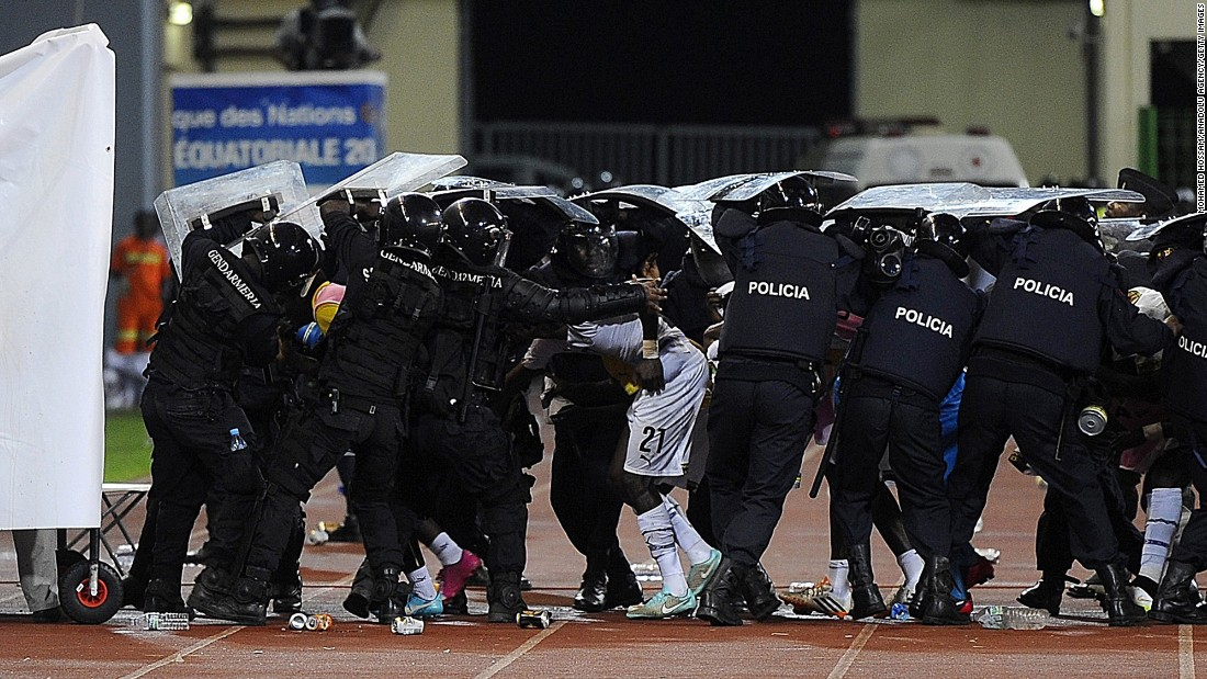 Police officers protect footballers from missiles thrown by fans.