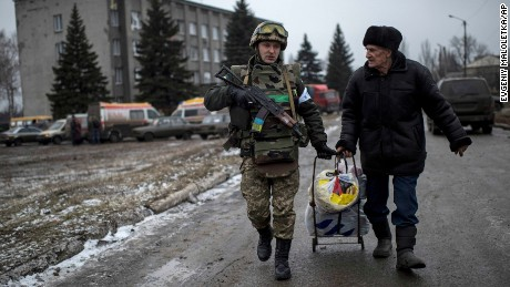 A Ukrainian serviceman helps an elderly man carry his possessions during the evacuation of Debaltseve, Ukraine, February 6.