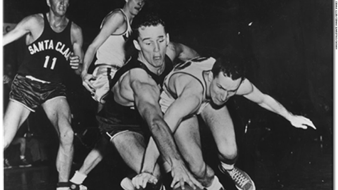 A member of the Kansas Jayhawks team that won the 1952 NCAA Championship, Smith, far right, dives for a loose ball during a game against Santa Clara University on March 25, 1952.