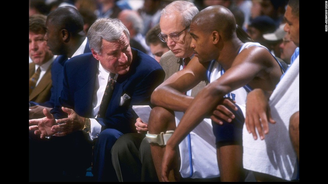 Smith confers with guard Vince Carter as assistant coach Bill Guthridge looks on December 6, 1996, during a game against the USC Trojans in Charlotte, North Carolina. Carter would go on to NBA greatness after UNC.