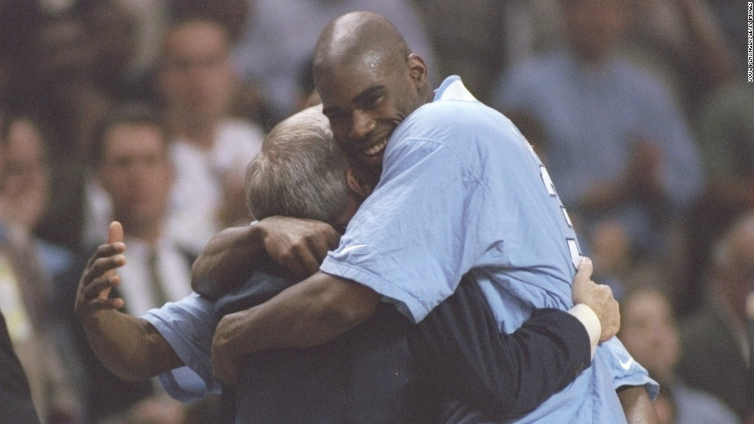 Foward Antawn Jamison hugs Smith on March 15, 1997, after a playoff game against the Colorado Buffaloes in Winston-Salem, North Carolina. Smith made his last of a career 11 Final Four appearances that year.