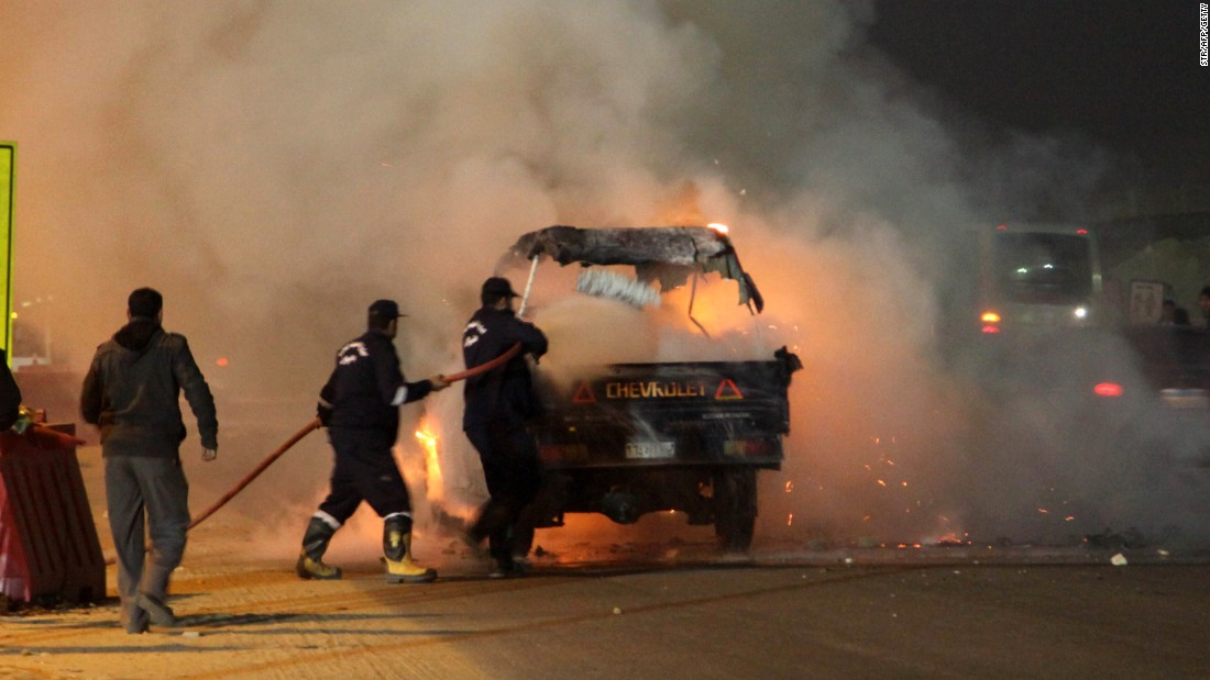 Firefighters try to put out the burning vehicle.