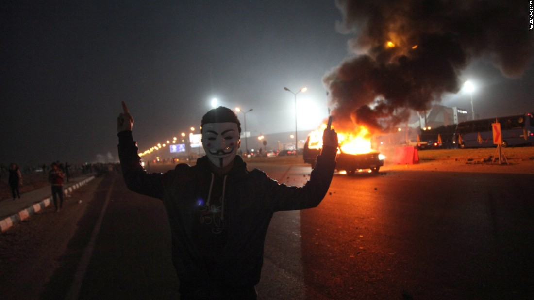 A masked man gestures near a burning car outside the stadium.