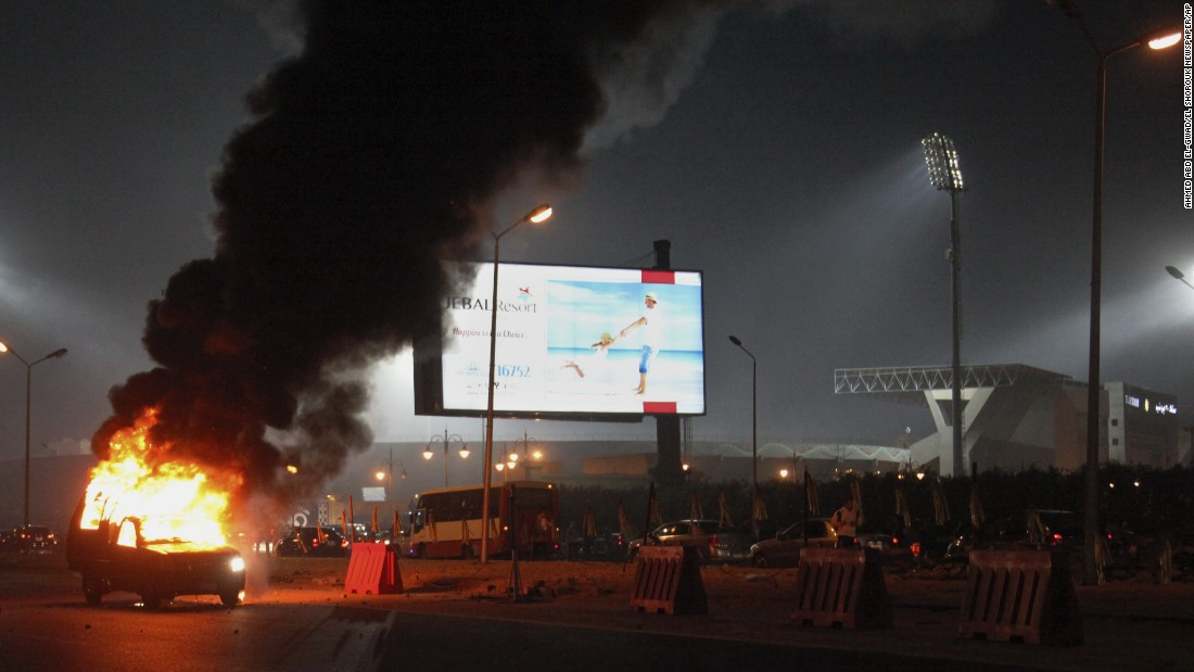 A pickup truck burns outside the stadium.