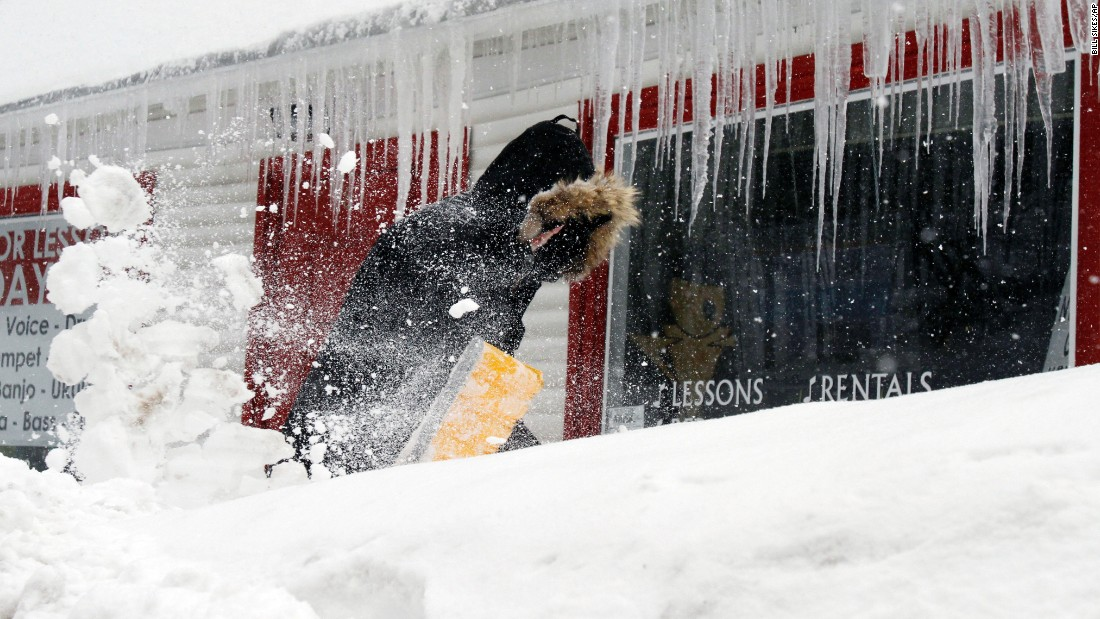 Corbit Larson clears snow in front of his Centre Music House store in Framingham, Massachusetts, on February 9.