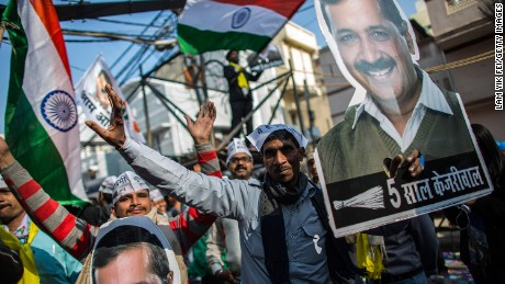 Aam Aadmi Party (AAP) supporters holding up images of Arvind Kejriwal celebrate in Delhi on February 10.