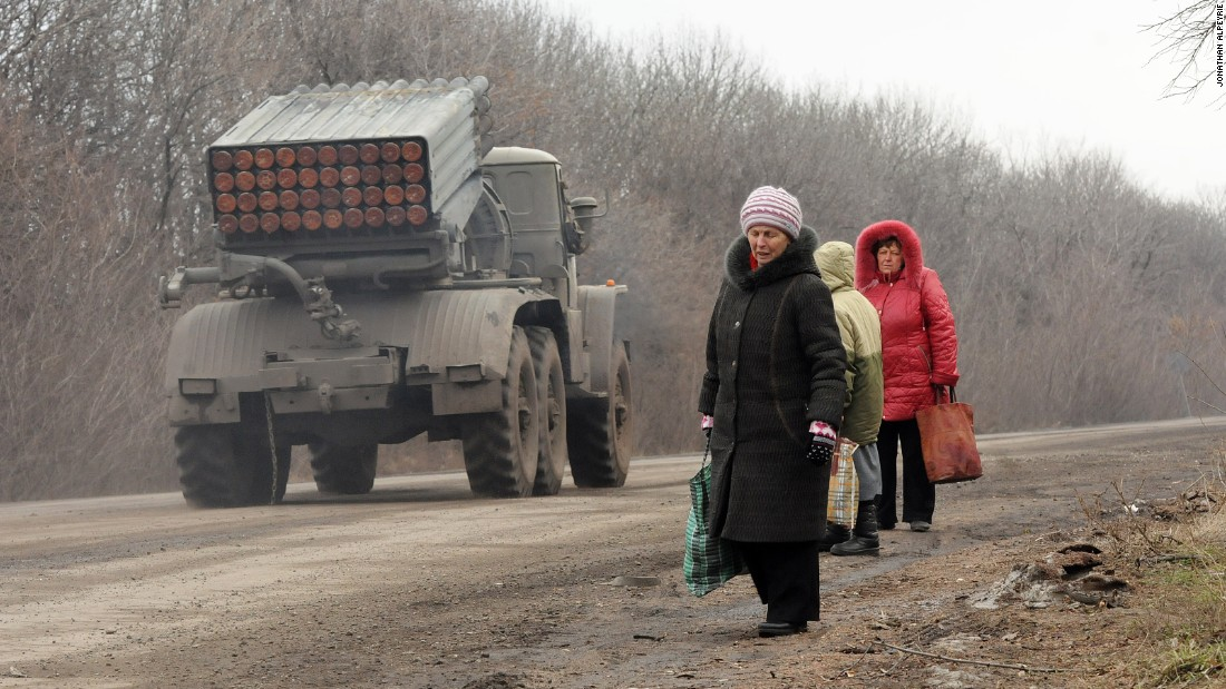 Refugees from Debaltseve escape the fighting while Grad missile systems head to the front on February 5, 2015. Fighting continues between Ukrainian forces and pro-Russian separatists in and around the important rail hub. The humanitarian situation  has become dire as thousands have fled the shelling, while many more are trapped. Residents use all manner of vehicles, driven by volunteers, to get out of the area.