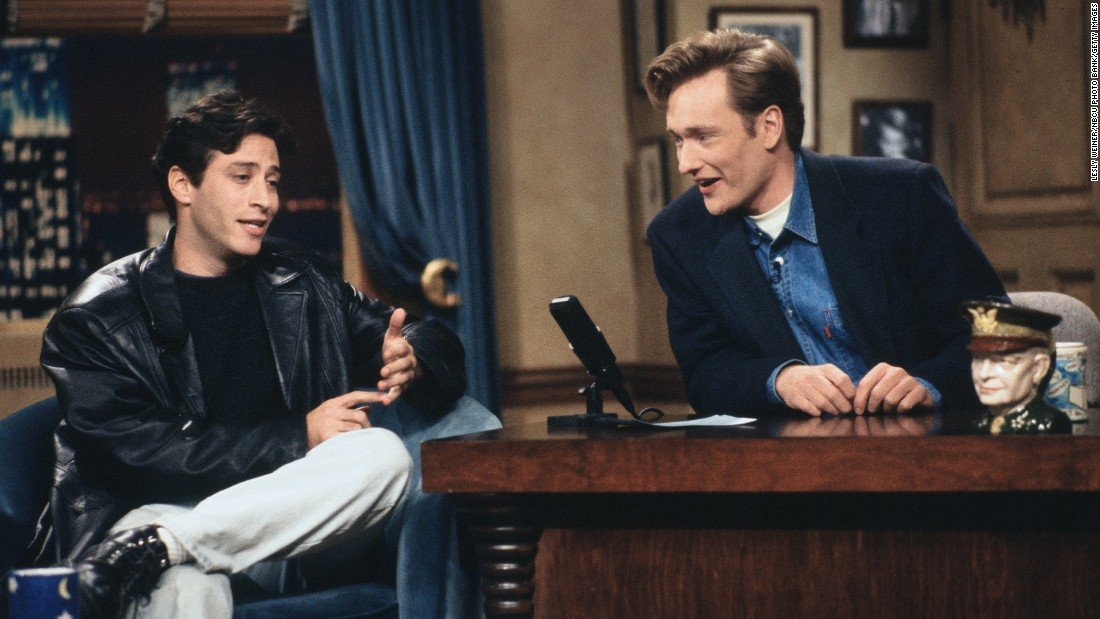 "He started as a stand-up comedian in New York, eventually becoming <a href=""http://www.cc.com/comedians/jon-stewart"" target=""_blank"">a regular</a> on HBO's ""The Larry Sanders Show."" He is seen here as a guest on a 1993 episode of ""Late Night with Conan O'Brien."""
