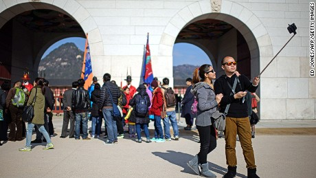 In a photo taken on November 26, 2014 a couple use a 'selfie stick' to take a photo before the Gyeongbokgung palace in central Seoul. In South Korea anyone selling an unregistered bluetooth-enabled selfie stick could face a 27,000 US dollar fine or up to three years in prison, the Science Ministry announced last week. The focus of the ministerial crackdown are those models that come with bluetooth technology, allowing the user to release the smartphone shutter remotely, rather than using a timer. As such they have to be tested and certified to ensure they don't pose a disruption to other devices using the same radio frequency. AFP PHOTO / Ed Jones        (Photo credit should read ED JONES/AFP/Getty Images)