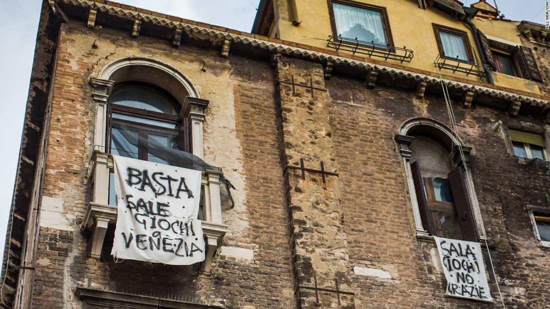 "An anti-Mafia banner, reading ""Enough - out of Venice"" hangs from a Venetian window above the canals."