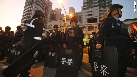 Police in riot gear gather outside a prison in Kaohsiung, Taiwan, as prisoners hold staff hostage inside.