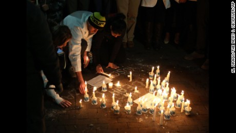 People light candles to honor the victims at UNC Chapel Hill on February 11.