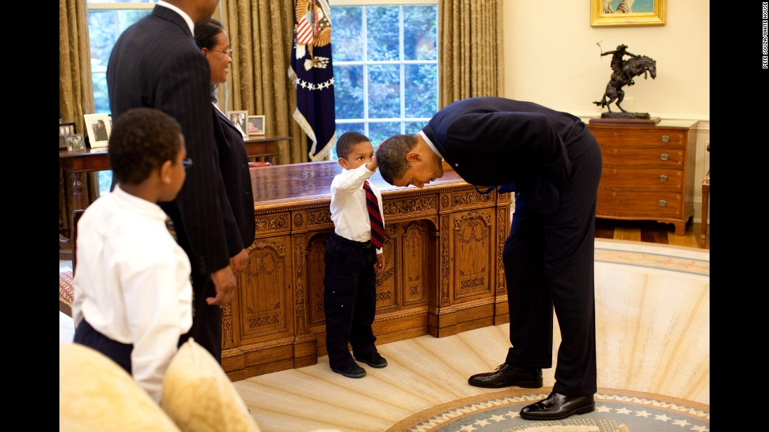 "Obama bends over so the son of a White House staff member can pat his head during a visit to the Oval Office in May 2009. The boy <a href=""http://newsroom.blogs.cnn.com/2009/05/15/hair-apparent/"" target=""_blank"">wanted to know </a>if Obama's hair felt like his."