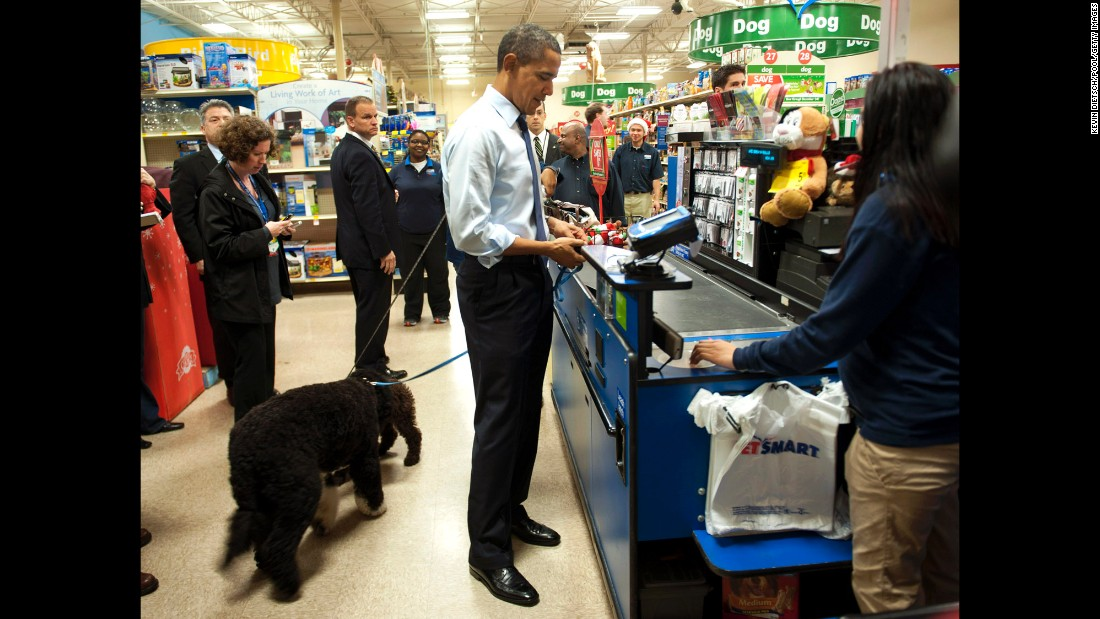 Obama pays for a dog toy as he shops with his dog Bo at a PetSmart in Alexandria, Virginia, in December 2011.