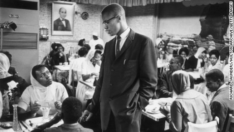 circa 1965:  Black nationalist and Muslim leader Malcolm X (1925 - 1965) talking to a woman inside Temple 7, a Halal restaurant patronized by black Muslims and situated on Lenox Avenue and 116th Street, Harlem, New York.  (Photo by Richard Saunders/Hulton Archive/Getty Images)