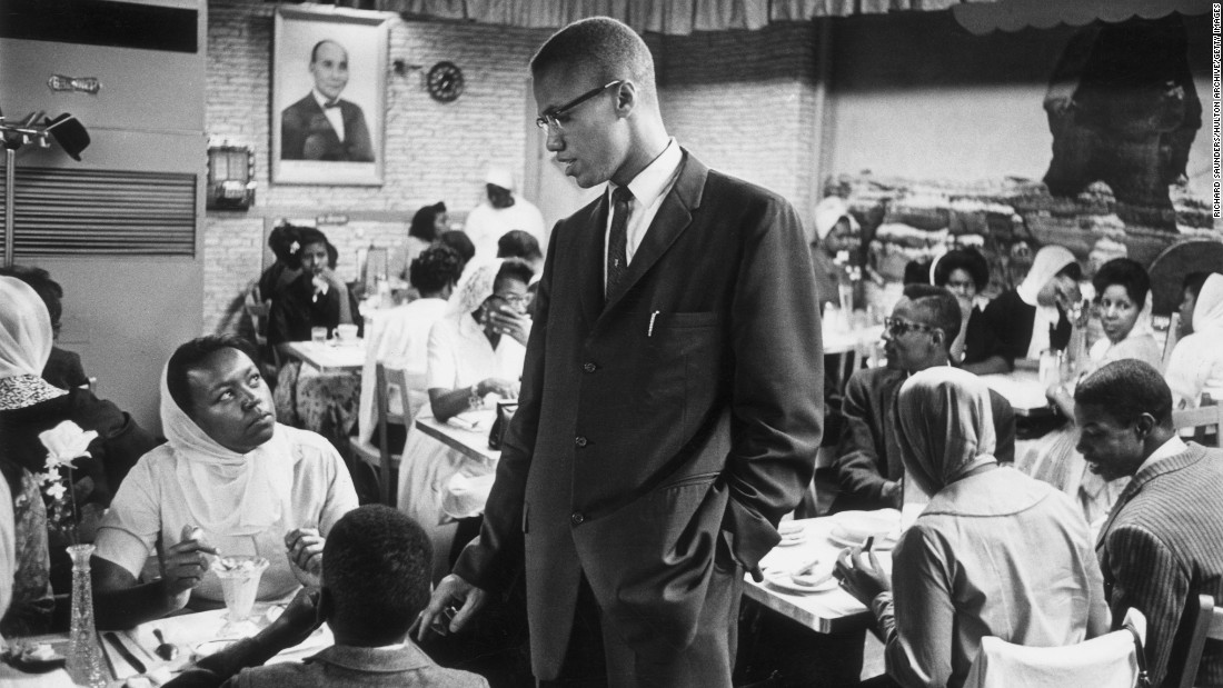 Malcolm X talks to a woman inside a Halal restaurant patronized by black Muslims in Harlem.