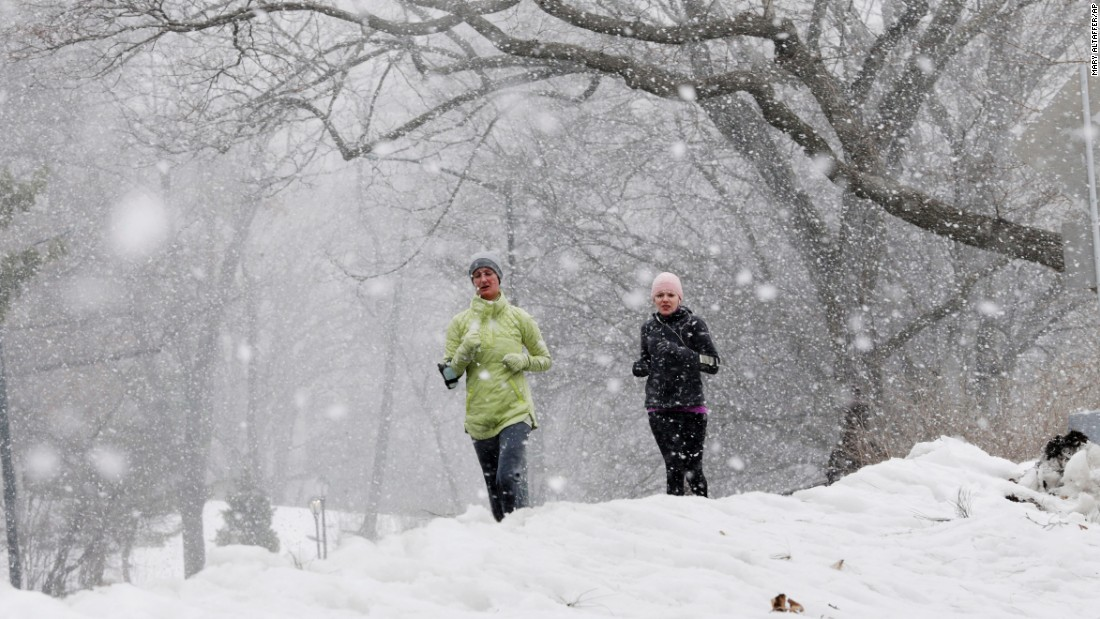 Joggers run in the snow, Thursday, February, 12, in New York's Central Park.