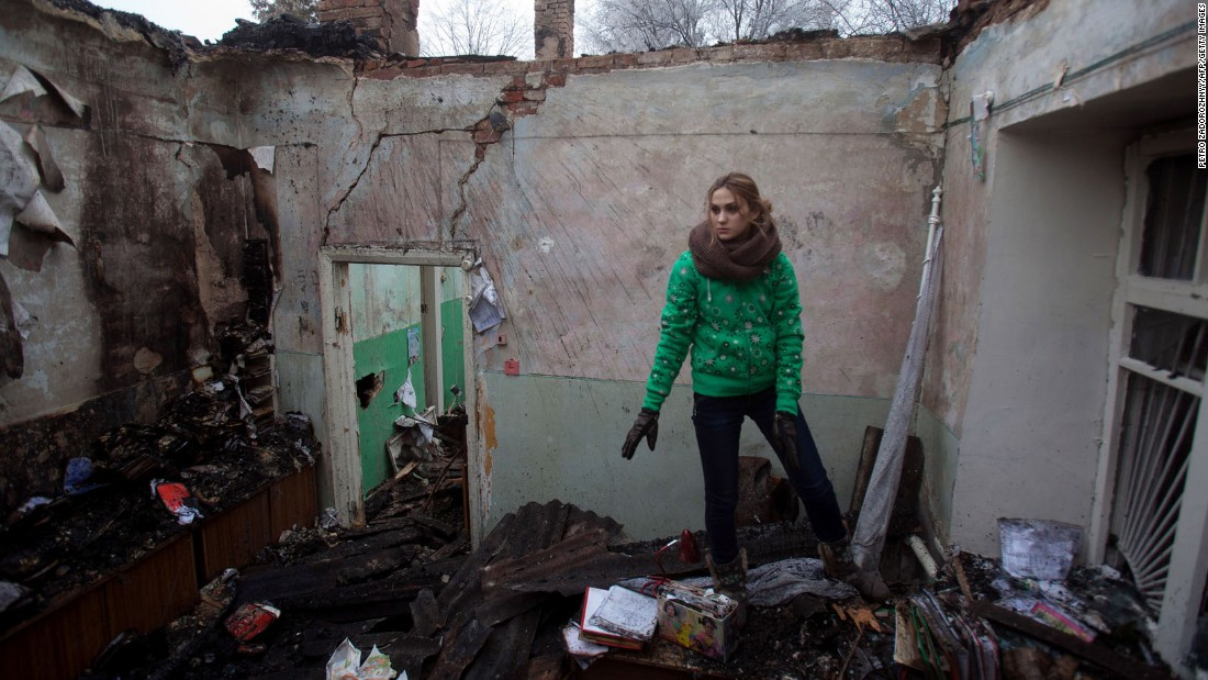 A woman salvages items February 15 from the rubble of a destroyed clinic where she had worked in Opytne, Ukraine.