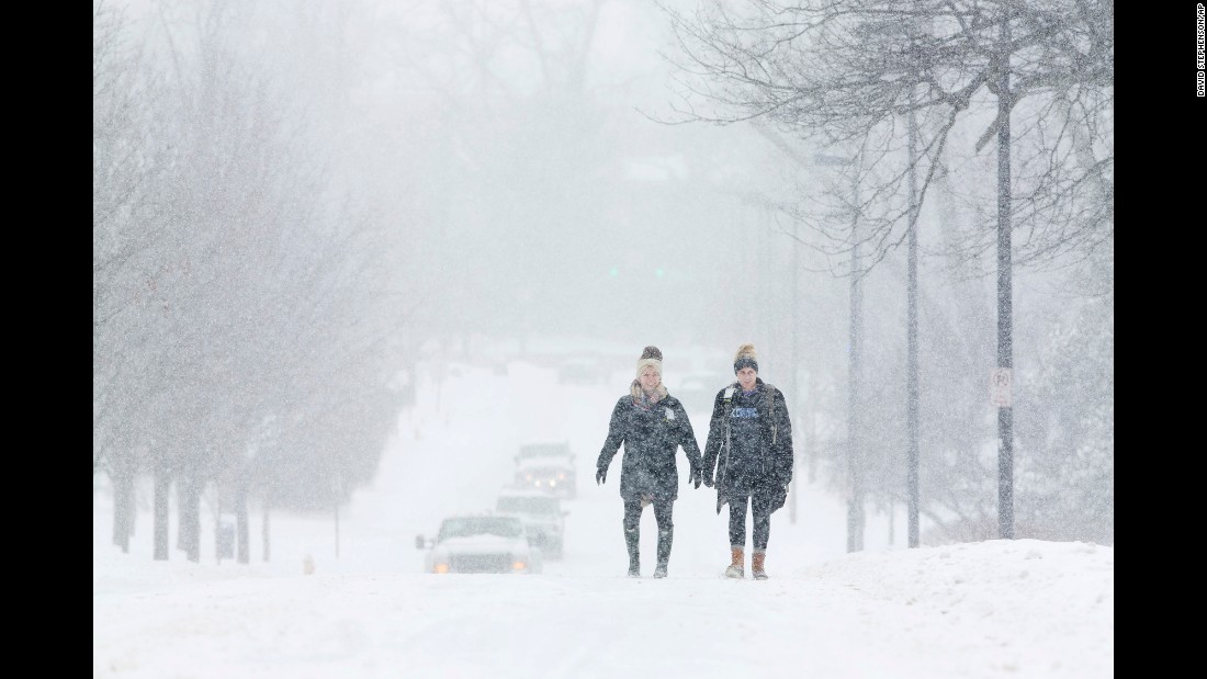 University of Kentucky students Courtney Wiseman, left, and Abby Lerner walk in the falling snow in Lexington, Kentucky, on February 16.