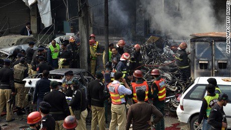 Pakistani police officials inspect the site after a bomb explosion near the police headquarters in Lahore on February 17, 2015.