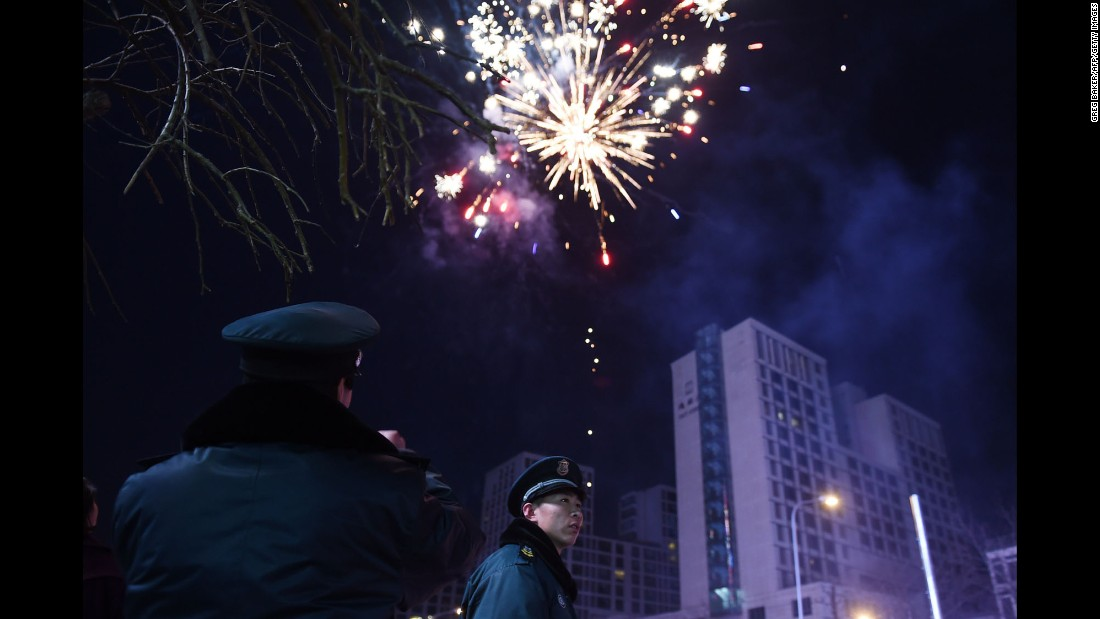 Security guards watch as fireworks go off on the eve of the Lunar New Year in Beijing on Wednesday, February 18.