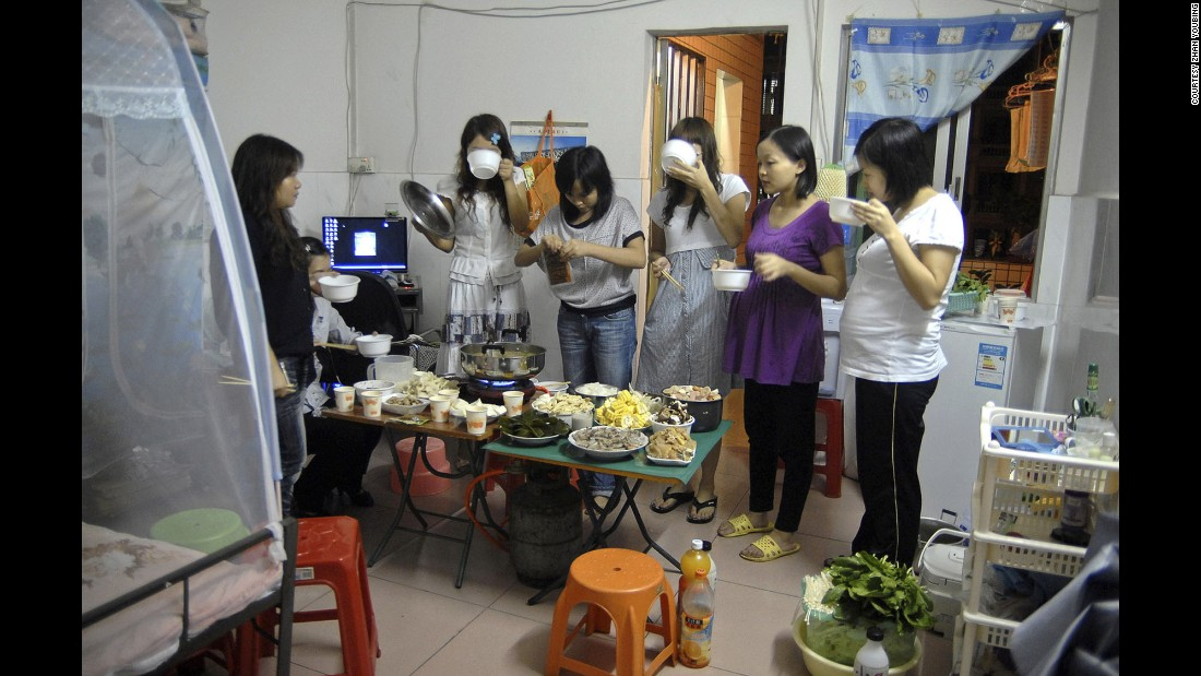 Migrant workers enjoy a dinner party in a rented room in Dongguan.