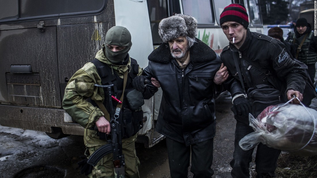 An elderly Ukrainian man is helped by a Ukrainian Army soldier and a citizen during a evacuation of civilians in Debaltseve.