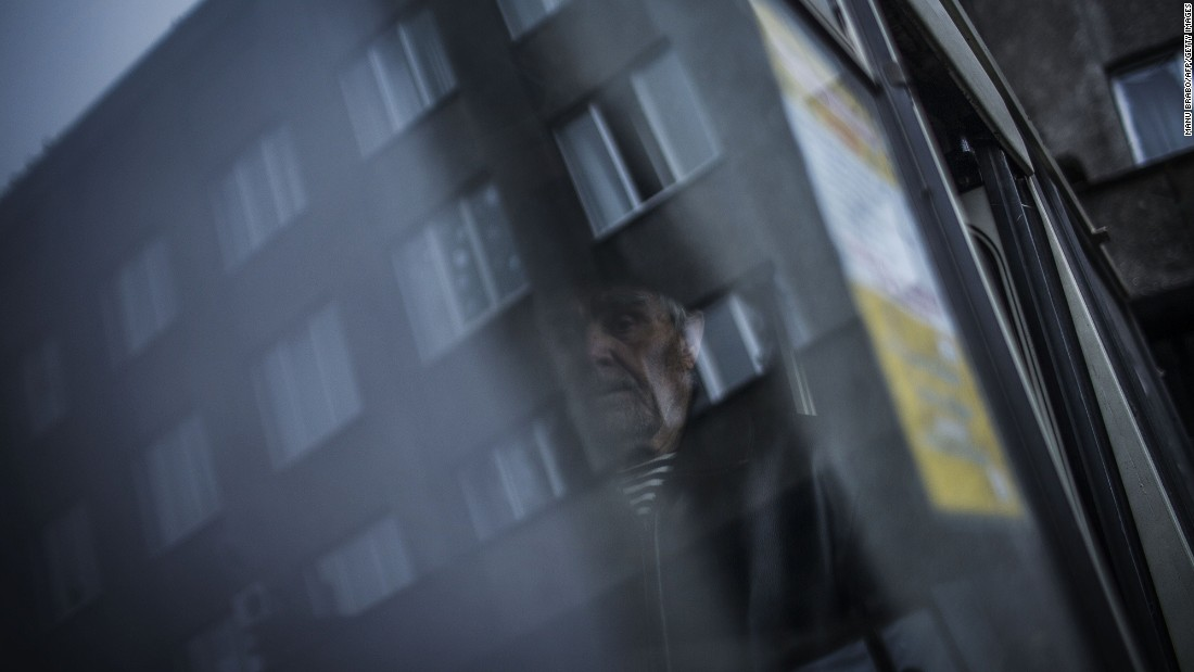 An elderly Ukrainian man stands inside a bus before being evacuated from the region.