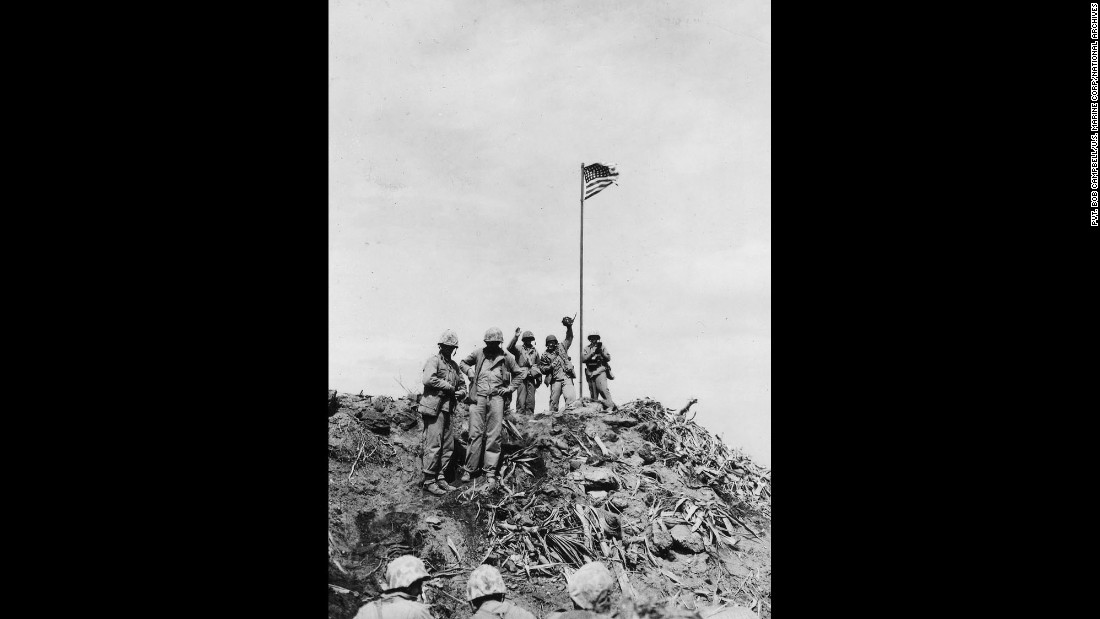 Marine Pfc. Bob Campbell shot this photo of Rosenthal standing with Marines near the first flag. Rosenthal can be seen waving his camera in the air.