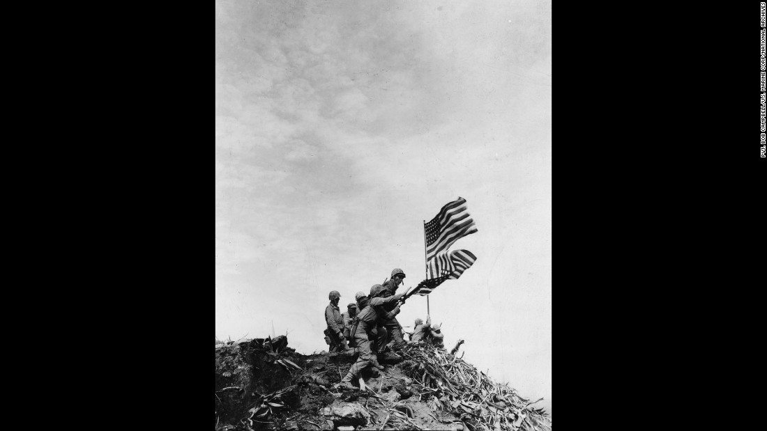 When Marines replaced the smaller flag with the bigger one, they lowered and raised the flags simultaneously, as seen in this photo by Campbell.