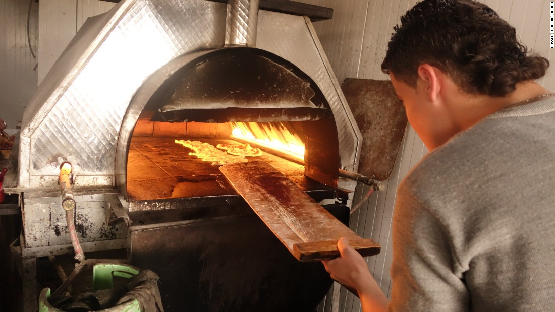 Pizzas bakes in an oven in the Zaatari camp, just across the border from Jordan. The pizza parlor's owner, Abu Mohamed, says his business his booming after he began offering pizza delivery by bicycle.