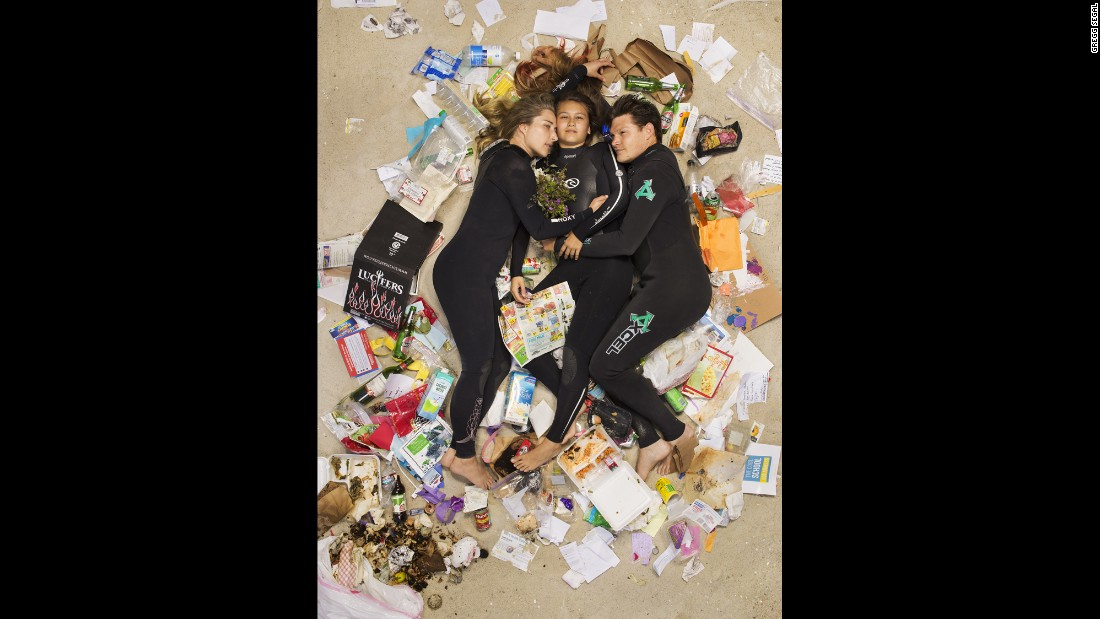 "Susan, Curtis and Brittany cuddled up on the beach in wetsuits in their ""7 Days of Garbage"" shoot."