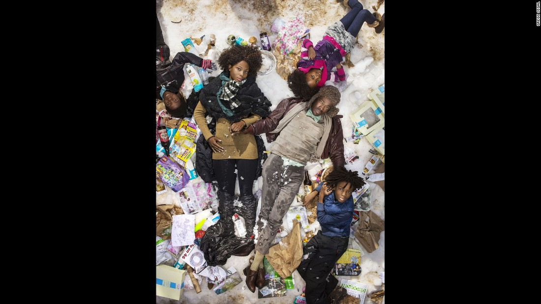 The Munroe family lies down in a snowy setting with a week of their trash.