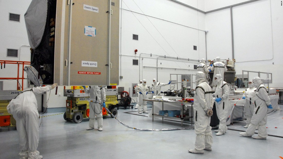 Workers check on the spacecraft, at left, as they prepare to mate it with the upper stage booster rocket on the right.