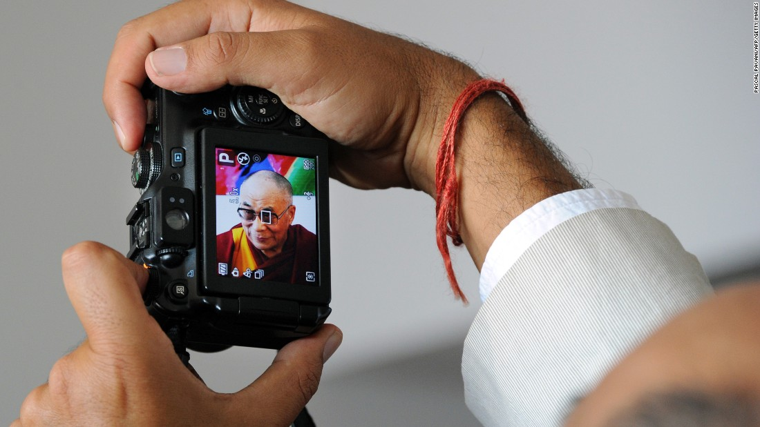 A man takes a picture of the Dalai Lama upon his arrival at the airport in Blagnac, France, on August 12, 2011. That same year, the leader approves amendments to the exiled constitution, formally removing his political and administrative responsibilities.