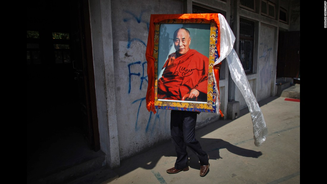 A Tibetan man in Katmandu, Nepal, carries a portrait of the Dalai Lama on April 25, 2012, during an event marking the 23rd birthday of Panchen Lama Gendun Choekyi Nyima, the second-highest Tibetan religious leader.
