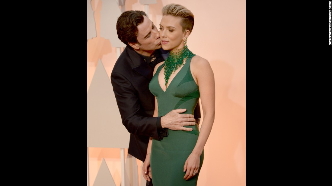 Travolta had a frisky night. Here he gives Scarlett Johansson a smooch and a squeeze on the red carpet.